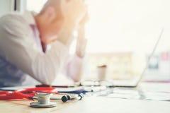 Das Stethoskop und Doktor, die mit Laptop sitzen, betonen Kopfschmerzen ungefähr Stockbild