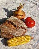 Das Stillleben mit Brot, Zwiebel, Mais, Tomate Stockfotografie