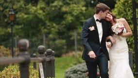 Das stilvolle lächelnde Jungvermähltenpaar geht glücklich entlang den grünen blühenden Garten und küsst zart stock video