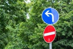 Das Straßenschild, das falsche Richtung und müssend nach links abbiegen zeigt Stockbilder
