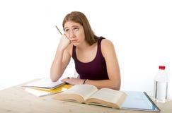 Das Studentmädchen, das für Hochschulprüfung studiert, sorgte sich im ermüdeten Druckgefühl und im Berstdruck stockfotografie