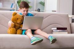 Das surfende Internet des kleinen Jungen auf Laptop stockfotografie
