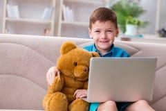 Das surfende Internet des kleinen Jungen auf Laptop stockfoto