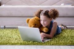 Das surfende Internet des kleinen Mädchens auf Laptop stockbild