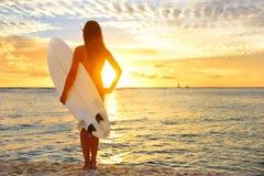 Das surfende Surfermädchen, das Ozean betrachtet, setzen Sonnenuntergang auf den Strand Stockbilder
