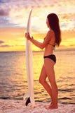 Das surfende Surfermädchen, das Ozean betrachtet, setzen Sonnenuntergang auf den Strand Stockfotografie