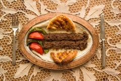 Das Türkische-Adana-Kebab auf einer rustikalen Tischdecke Stockfotos