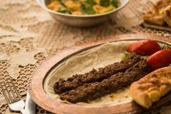 Das Türkische-Adana-Kebab auf einer rustikalen Tischdecke Stockfoto