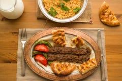 Das Türkische-Adana-Kebab mit Bulgur Reis und ayran Stockfotografie