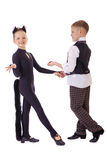 Das tanzende kleine Mädchen, das als Katze gekleidet werden und ein Junge in einem Plaid bekleiden Lizenzfreie Stockbilder