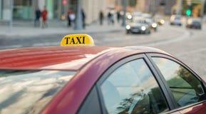 Das Taxi, das auf dem Bürgersteig einer großen Straße mit großen Staus, das Auto geparkt wird, reflektiert die Lichter der Abends stockbild