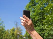 Das Telefon in der Hand der alten Frau auf dem Hintergrund des blauen Himmels Lizenzfreie Stockfotografie