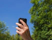 Das Telefon in der Hand der alten Frau auf dem Hintergrund des blauen Himmels Lizenzfreies Stockfoto