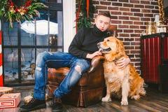 Das Thema ist die Freundschaft des Mannes und des Tieres Kaukasischer junger Mannes- und Schoßhundzucht Labrador-golden retriever lizenzfreie stockfotos