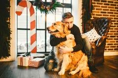 Das Thema ist die Freundschaft des Mannes und des Tieres Kaukasischer junger Mannes- und Schoßhundzucht Labrador-golden retriever stockfotografie
