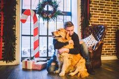 Das Thema ist die Freundschaft des Mannes und des Tieres Kaukasischer junger Mannes- und Schoßhundzucht Labrador-golden retriever lizenzfreie stockbilder