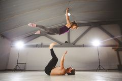 Das Thema von Acroyoga und von Yoga-Haltungen Acroyogis Üben mit Studio Hintergrundbeleuchtung der niedrige Mann wirft den Knallf Stockfotografie