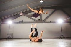 Das Thema von Acroyoga und von Yoga-Haltungen Acroyogis Üben mit Studio Hintergrundbeleuchtung der niedrige Mann wirft den Knallf Lizenzfreie Stockfotos