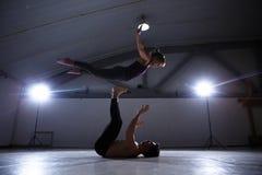 Das Thema von Acroyoga und von Yoga-Haltungen Acroyogis Üben mit Studio Hintergrundbeleuchtung der niedrige Mann wirft den Knallf Stockbild