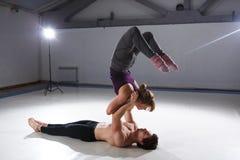 Das Thema von Acroyoga und von Yoga-Haltungen Acroyogis Üben mit Studio Hintergrundbeleuchtung die Mann Basisgriffe im Static Stockbild
