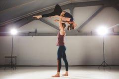 Das Thema von Acroyoga und von Yoga-Haltungen Ein Paar von zwei Männern und von Frau stehen in der Position von asana Der Kerl hä Stockbild