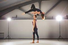 Das Thema von Acroyoga und von Yoga-Haltungen Ein Paar von zwei Männern und von Frau stehen in der Position von asana Der Kerl hä Stockfotografie