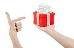 Das Thema von Feiern und von Geschenken: übergeben Sie das Halten eines Geschenks eingewickelt im roten Kasten mit weißem Band un Stockfotos