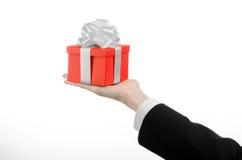 Das Thema von Feiern und von Geschenken: ein Mann in einem schwarzen Anzug, der ein exklusives Geschenk eingewickelt im roten Kas Stockbild