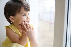 Das Träumen des Porträts des kleinen Mädchens lehnt sich auf Ellbögen auf dem Fenster, das etwas herbeisehnt Kind, das an angeneh Stockfotografie