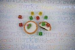 Das traditionelle Weihnachtslebensmittel-Fotografiebild zerkleinern Torten mit miniture roten grünen gelben Weihnachtsgeschenk-Ba Stockfotos
