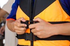 Das tragende Setzen des jungen Reisenden auf eine Schwimmweste vor erhalten im Th stockfotografie