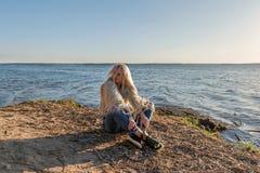 Das traurige grimmige blonde Mädchen, das auf der Küste mit dem schlampigen Haar im Lebensstil sitzt, kleidet Lizenzfreies Stockbild