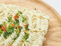 Das trockene Gemüse, das auf sofortigen Nudeln übersteigt, diente auf hölzernem Teller Lizenzfreie Stockfotografie