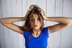 Das umgekippte Mädchen, das Haar überreicht hält herein, weißen hölzernen Hintergrund lizenzfreies stockbild