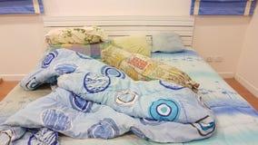 Das unordentliche des Kissens und der Decke auf dem Bett Stockbilder