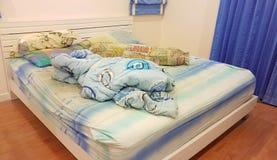 Das unordentliche des Kissens und der Decke auf dem Bett Lizenzfreies Stockfoto