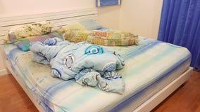 Das unordentliche des Kissens und der Decke auf dem Bett Stockfotos