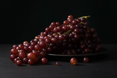 Das uvas vida roxa ainda no fundo preto Fotos de Stock Royalty Free