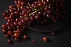 Das uvas vida roxa ainda no fundo preto Imagens de Stock