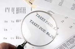 Das Vergrößerungsglas, welches die Wörter zeigt, besteuert zahlendes und Schuld auf Finanzpapier Lizenzfreie Stockfotos