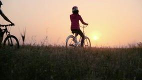 Das verheiratete Paar zieht auf Fahrräder gegen das aufgehende Sonne um stock video