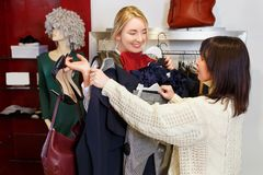 Das Verkäuferhelfen wählt Kleidung lizenzfreie stockbilder