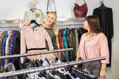 Das Verkäuferhelfen wählt Kleidung stockfotografie