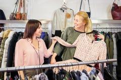 Das Verkäuferhelfen wählt Kleidung stockfoto