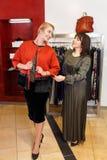 Das Verkäuferhelfen wählt Kleidung lizenzfreies stockfoto