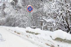 Das Verkehrsschild wird mit einer Schneeschicht umfasst Stockfoto
