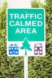 Das Verkehrszeichen, das VERKEHR angibt, BERUHIGTE BEREICH mit Bildern von Häusern Stockbild