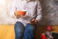 Das verwendende intelligente Telefon des Mannes mit Schale frischem Kaffee Stockfotografie
