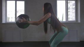 Das vorbildliche Handeln der athletischen Eignung der jungen Frau hockt Übung für die Hinterteile mit einem fitball stock footage