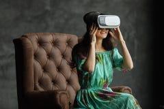 Das VR-Kopfhörerdesign ist generisch und keine Logos, Frau mit Gläsern virtueller Realität, sitzt in einem Stuhl, gegen einen dun lizenzfreies stockbild